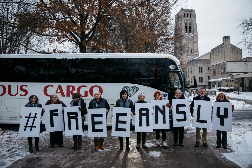 Riders showcase their #FREEANSLY signs before the bus ride from Saint Paul's Episcopal Church in Cleveland Heights, Ohio, to