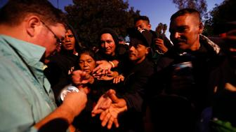An American well-wisher, left, is swarmed by migrants as he hands out canned soup, adding his efforts to those of many local Mexican groups distributing food, outside of a sports complex where more than 5,000 Central Americans are sheltering, in Tijuana, Mexico, Wednesday, Nov. 28, 2018. As Mexico wrestles with what to do with the thousands of people camped out in the border city of Tijuana, President-elect Andres Manuel Lopez Obrador's government signaled Tuesday that it would be willing to house the migrants on Mexican soil while they apply for asylum in the United States, a key demand of U.S. President Donald Trump. (AP Photo/Rebecca Blackwell)
