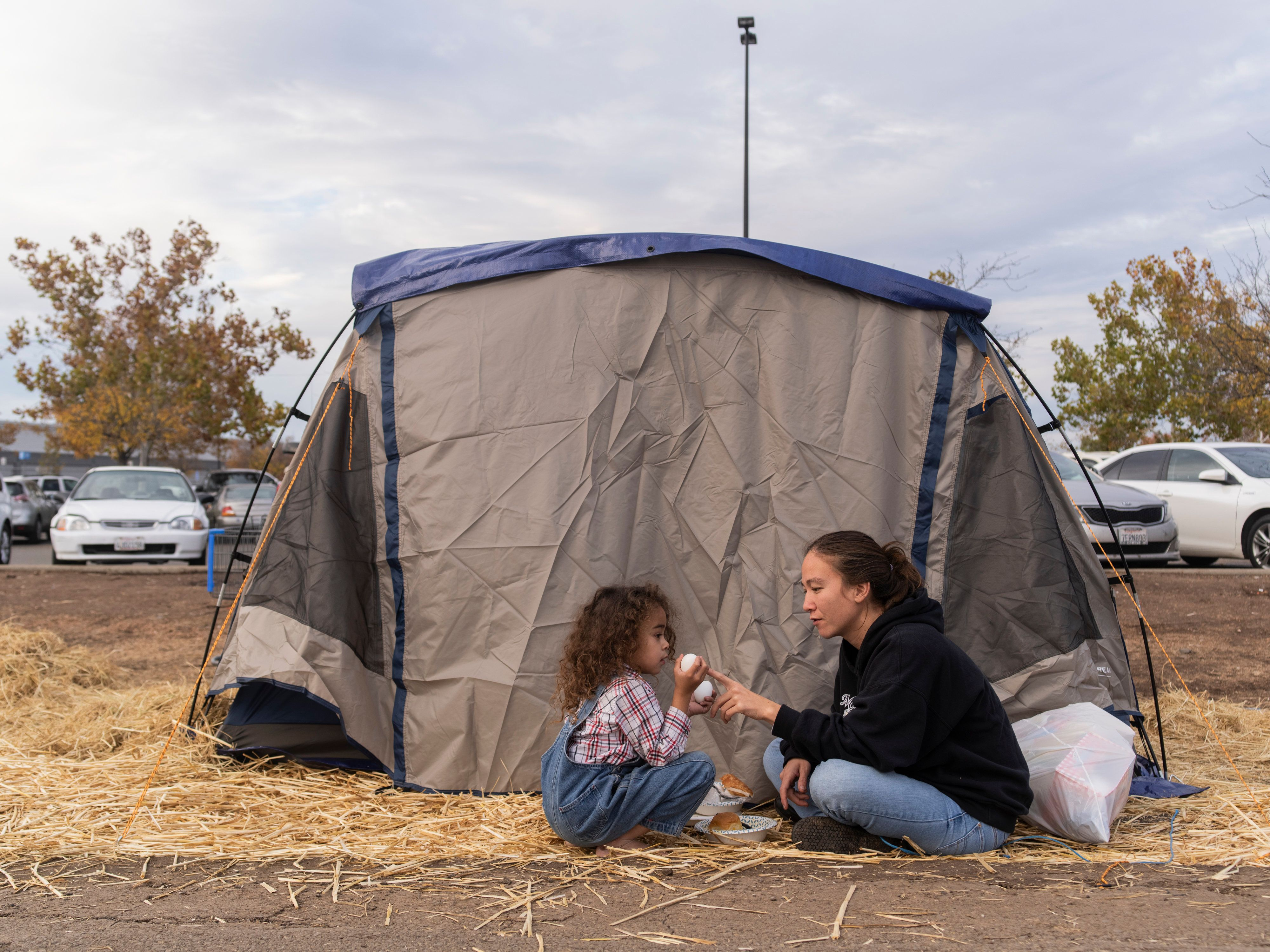 Rubyjade Stewart and her son, Rene, eat lunch at their tent in the Walmart lot on Wednesday between rain showers. By Thursday