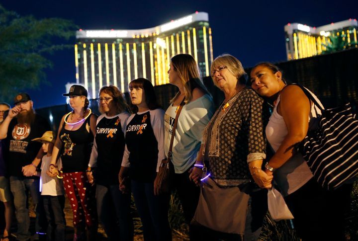 Survivors of the Oct. 1, 2017, mass shooting in Las Vegas form a chain around the shuttered site of a country music festival on the first anniversary of the shooting. The Justice Department has awarded more than $16 million to the victims.