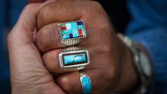 A close-up shot of Native American turquoise rings on a man's hand.