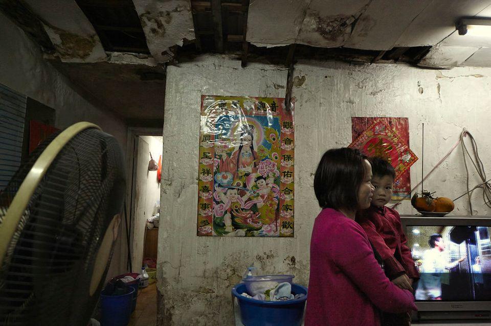 Eine junge Familie in einer von vielen schlecht erhaltenen, unterteilten Wohnungen in Hongkong. Die durchschnittliche Wartezeit auf den öffentlichen Wohnungsbau beträgt 5,5 Jahre.