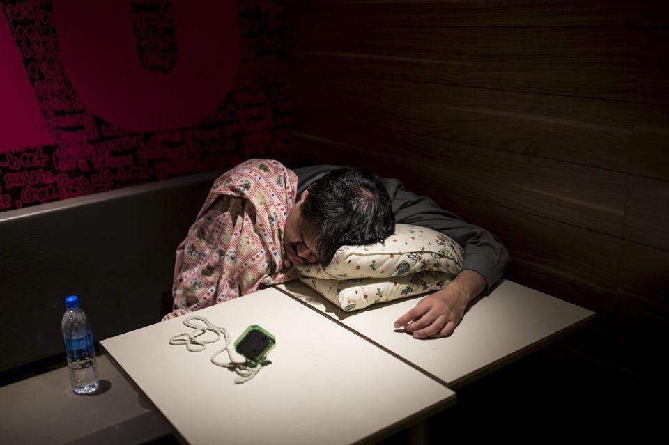 Einer der McRefugees aus Hongkong schläft in einem 24-Stunden-McDonald's. Er hat einen Wecker dabei.