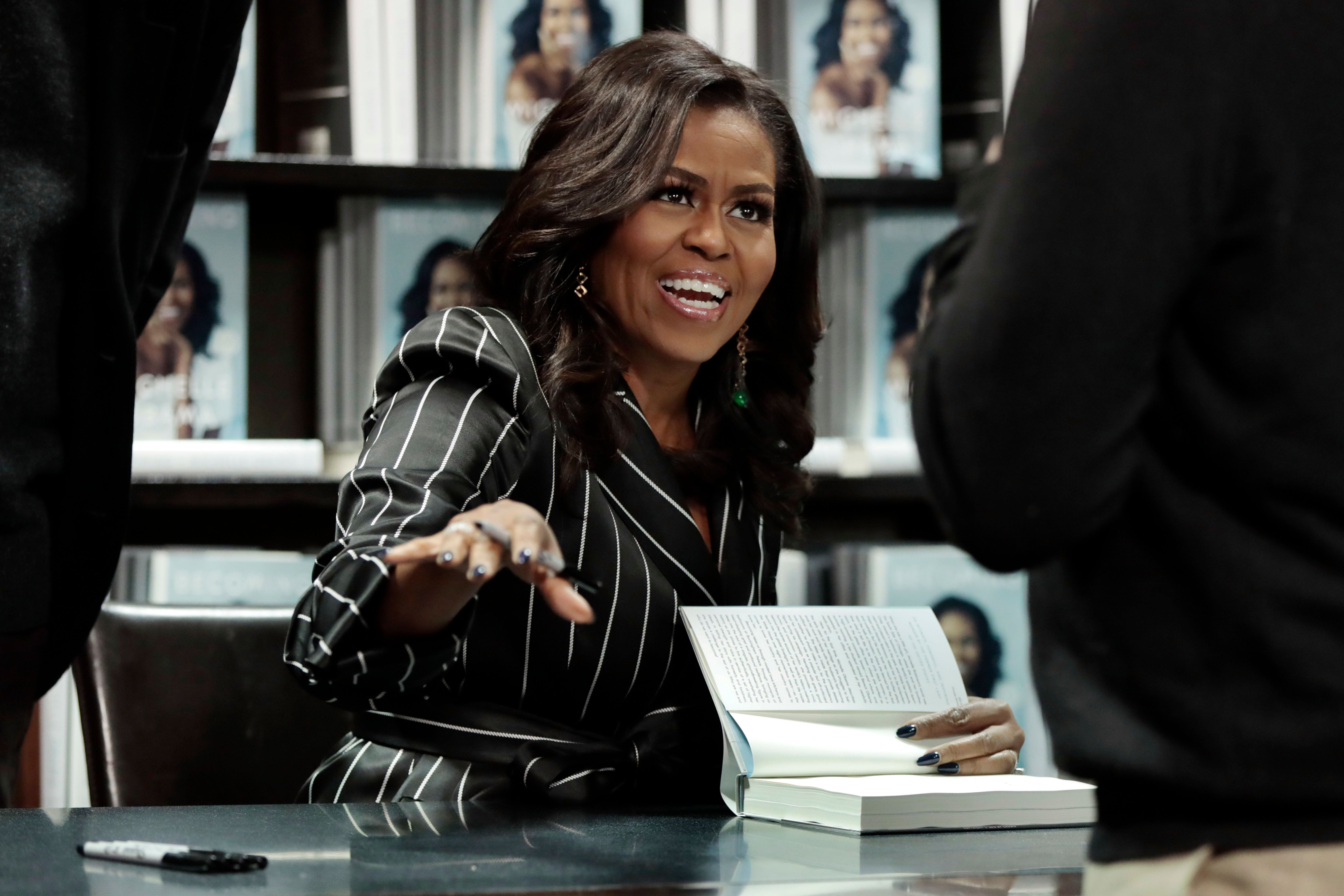 """Former First Lady Michelle Obama signs books during an appearance for her book, """"Becoming,"""" in New York, Friday, Nov. 30, 2018. Combined hardcover, e-book and audio sales in the U.S. and Canada topped 2 million copies in the first 15 days, Crown Publishing announced Friday. (AP Photo/Richard Drew)"""