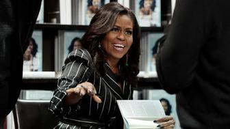 "Former First Lady Michelle Obama signs books during an appearance for her book, ""Becoming,"" in New York, Friday, Nov. 30, 2018. Combined hardcover, e-book and audio sales in the U.S. and Canada topped 2 million copies in the first 15 days, Crown Publishing announced Friday. (AP Photo/Richard Drew)"