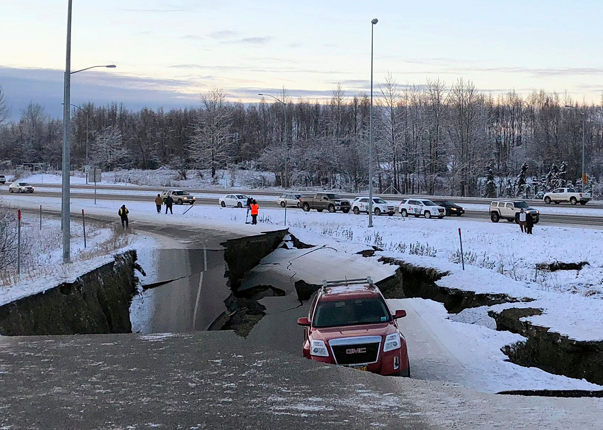 A car is trapped on a collapsed section of the offramp of Minnesota Drive in Anchorage, Friday, Nov. 30, 2018. Back-to-back earthquakes measuring 7.0 and 5.8 rocked buildings and buckled roads Friday morning in Anchorage, prompting people to run from their offices or seek shelter under office desks, while a tsunami warning had some seeking higher ground.