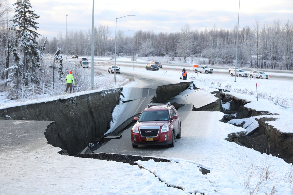 A vehicle sits stranded on a collapsed roadway near the airport after a major earthquake hit Anchorage, Alaska, on Nov. 30, 2