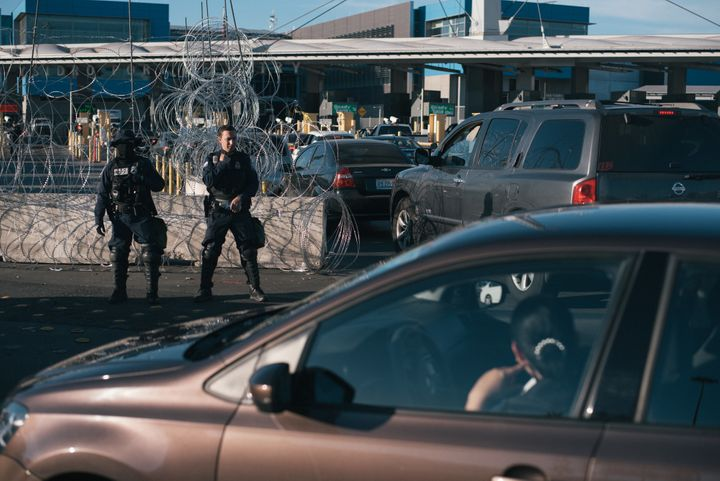 U.S. Customs and Border Protection officers observe vehicles standing in line at the San Ysidro port of entry in Tijuana, Mex