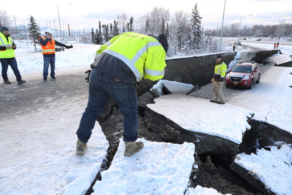 Workers check the damage along that roadway near the airport in Anchorage.