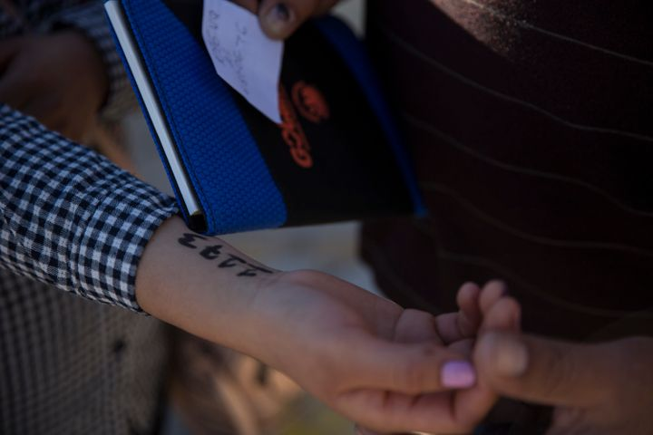 A woman from southern Mexico holds out her arm where administrators at Casa Del Migrante wrote a number on her arm to hold he