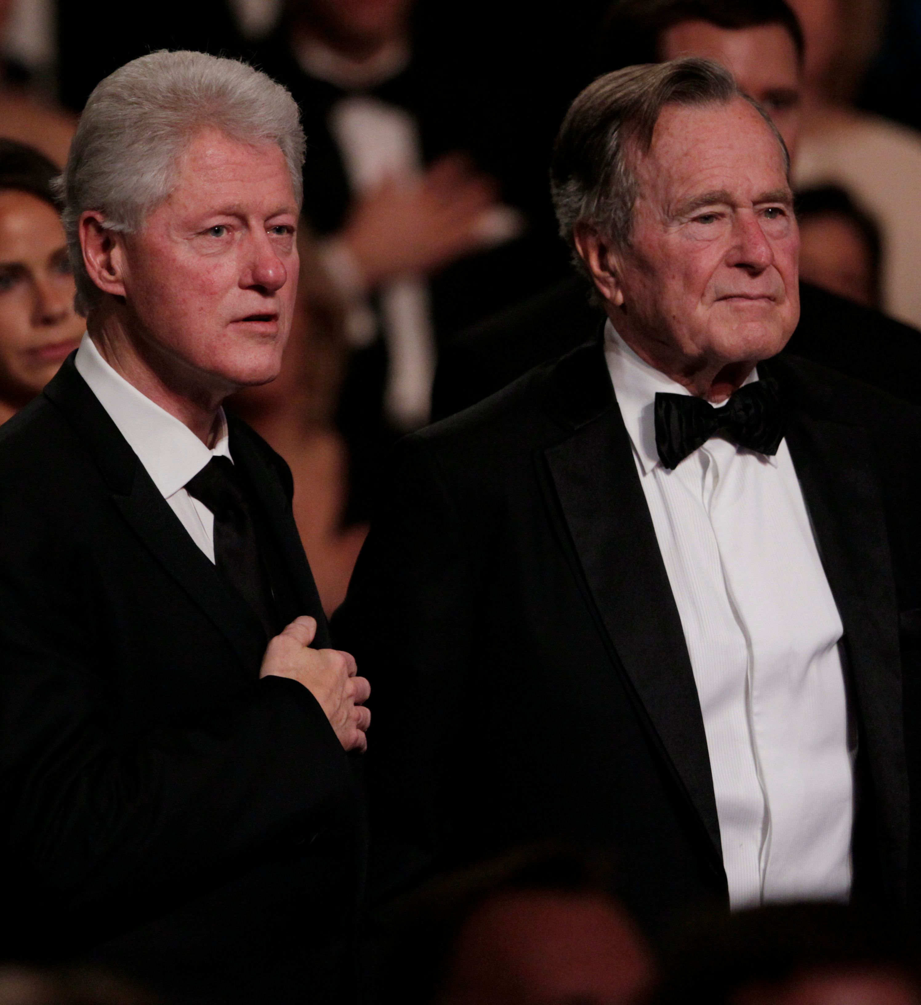 "From left, former President Bill Clinton, left and former President George H. W. Bush stand for the National Anthem at the Kennedy Center, Monday, March 21, 2011, in Washington, before the ""All Together Now - A Celebration of Service"" performance in honor of former President George H. W. Bush.  (AP Photo/Carolyn Kaster)"