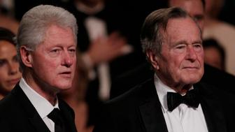 """From left, former President Bill Clinton, left and former President George H. W. Bush stand for the National Anthem at the Kennedy Center, Monday, March 21, 2011, in Washington, before the """"All Together Now - A Celebration of Service"""" performance in honor of former President George H. W. Bush.  (AP Photo/Carolyn Kaster)"""