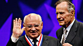 Mikhail Gorbachev, left, the former Soviet leader and Nobel Peace Prize winner, acknowledges the audience after being presented with the 2008 Liberty Medal by former U.S. President George H.W. Bush, Chairman of the National Constitution Center, during a ceremony at the center, Thursday, Sept. 18, 2008, in Philadelphia. Gorbachev is being honored for his role in ending the Cold War.   (AP Photo/Tom Mihalek)