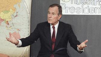 Fifth-grade students Guadalupe Guzman, left, and Ana Zamora, right, listen to U.S. President George H. Bush during his visit to Pickard Elementary School, Monday, Nov. 20, 1989 in Chicago. Bush visited the school after receiving a letter from Zambia asking his help in ridding her neighborhood from drugs. (AP Photo/Marcy Nighswander)