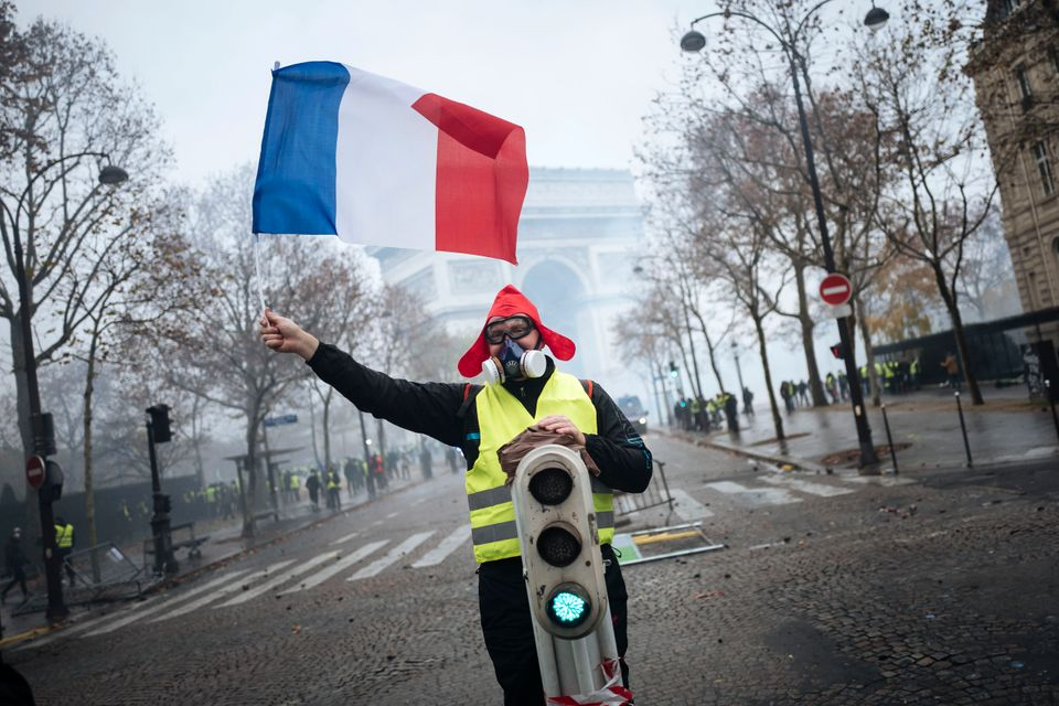 A demonstrator holds a French flag near the Arc de Triomphe.
