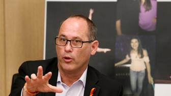 "FILE- In this May 24, 2018 file photo, Fred Guttenberg speaks at a news conference, in Miami. Guttenberg speaks next to photos of his daughter Jaime Guttenberg, who was one of 17 killed in the Valentine's Day massacre at Marjory Stoneman Douglas High School in Florida. Fred Guttenberg will start his Thanksgiving morning at a cemetery. ""This Thanksgiving is about loss,"" said Guttenberg who will visit Jaime's grave along with his wife, son and their two dogs. ""It's my first Thanksgiving without my daughter and we're not going to leave her out of it."" (AP Photo/Wilfredo Lee, File)"