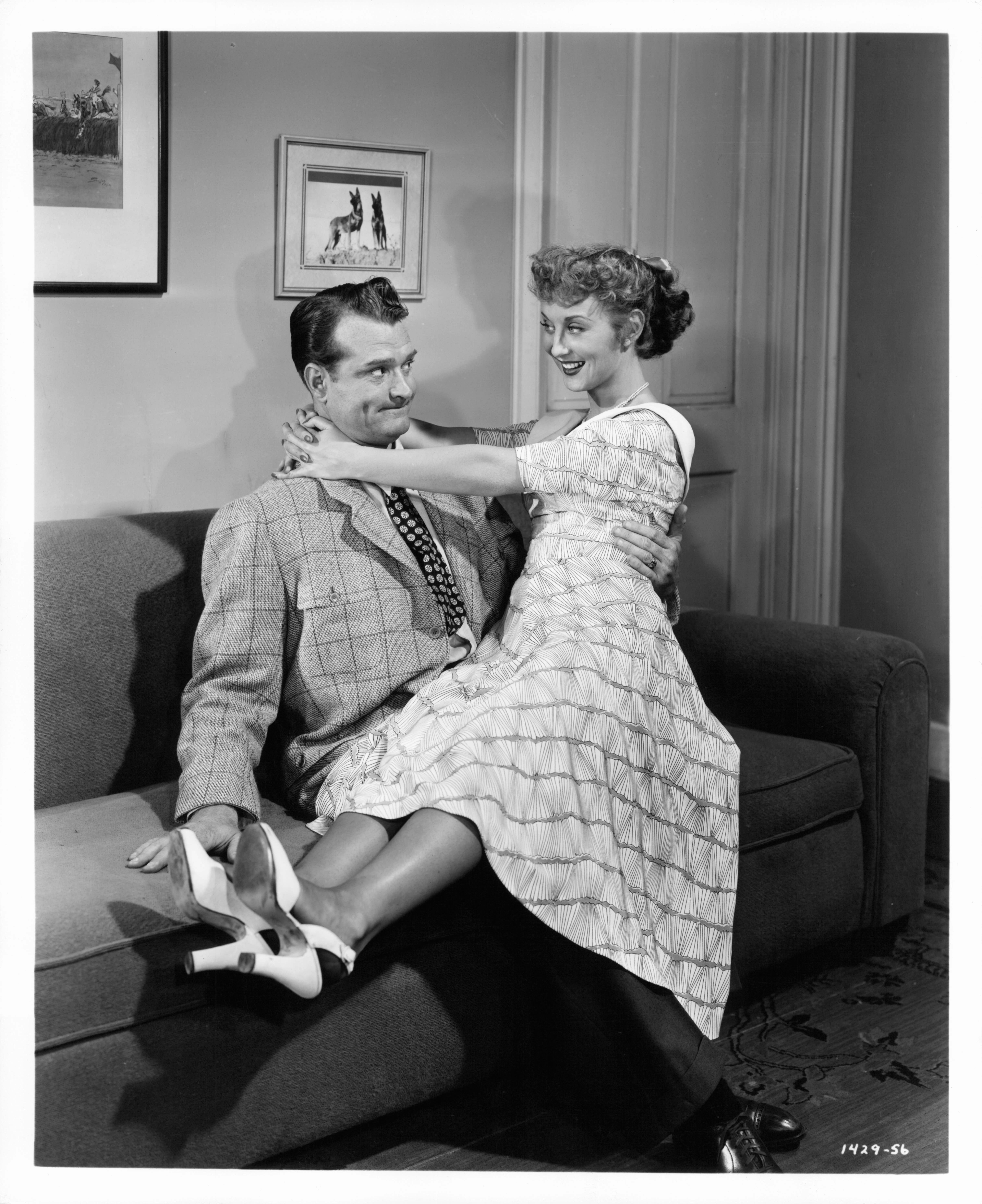 Betty Garrett sitting on Red Skelton's lap in a scene from the film 'Neptune's Daughter', 1949. (Photo by Metro-Goldwyn-Mayer/Getty Images)