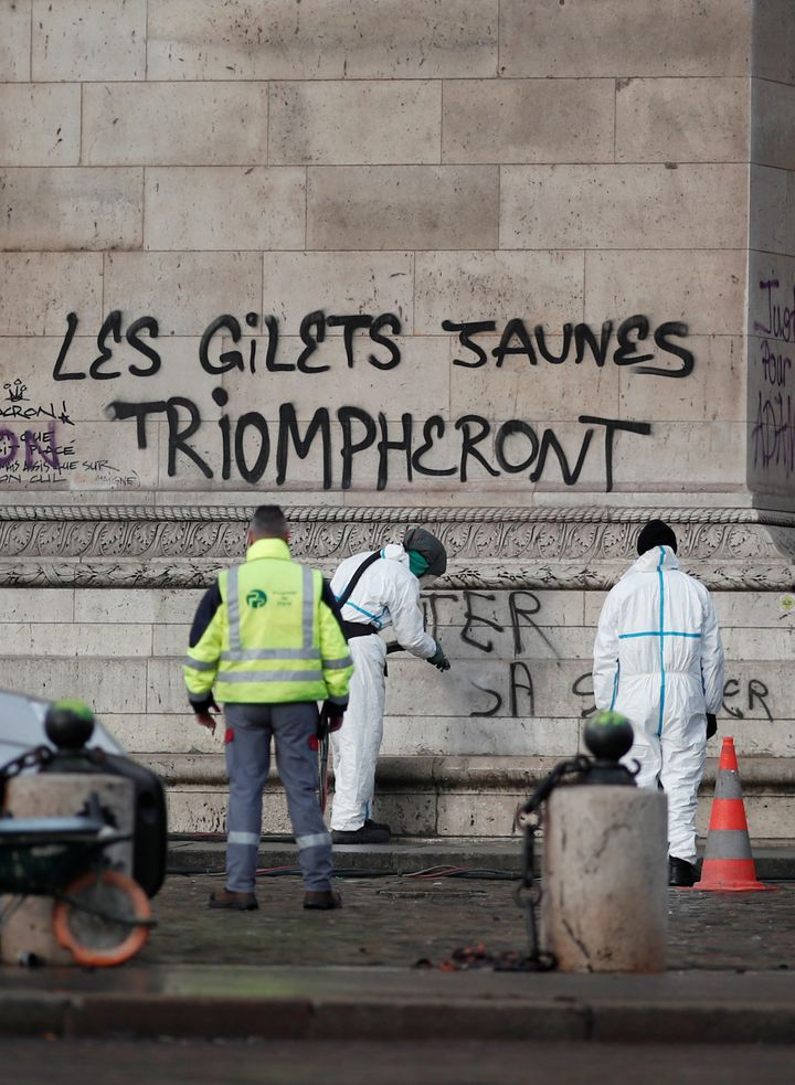 Professional cleaners begin to scrub graffiti from a monument in central Paris on Sunday.