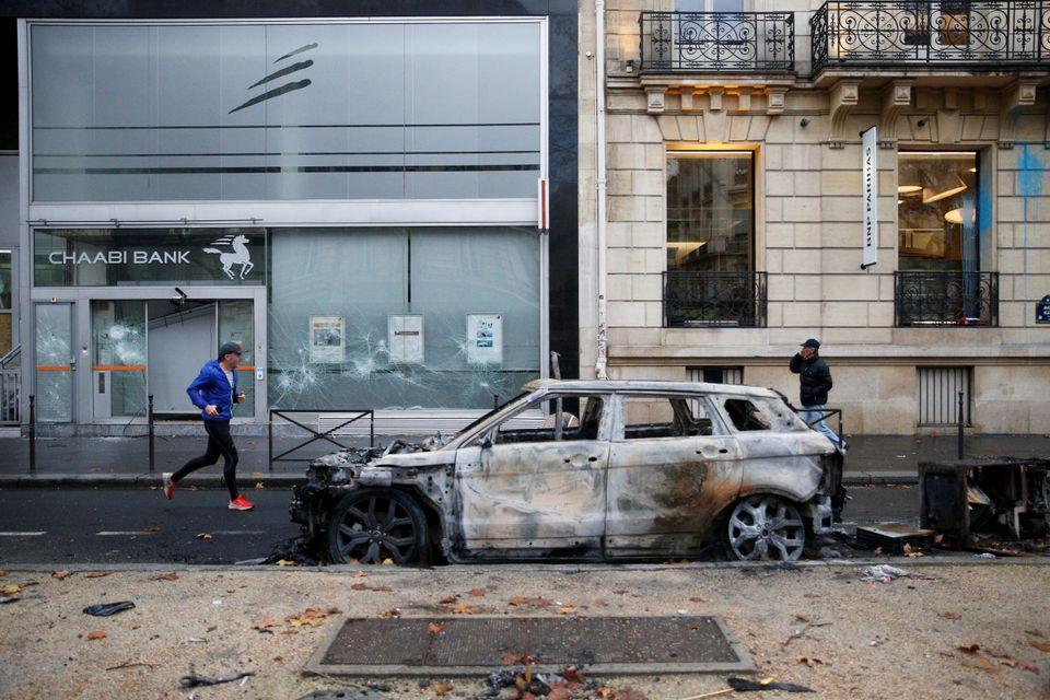 A Parisian runs beside a burnt-out car on