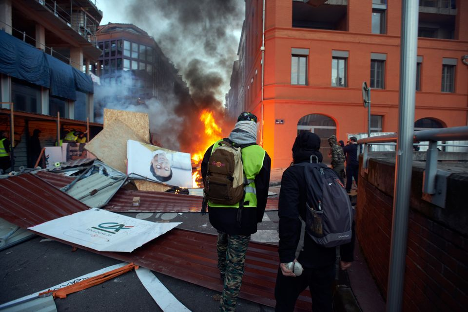 Rioters stand near flames and a barricade on