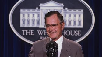 ***FILE PHOTO*** George H.W. Bush Has Passed Away Washington, DC. 1990 President George H. W. Bush stands at the podium as he responds to reporters questions during a news conference in the press briefing room at the White House. Credit: Mark Reinstein Credit: Mark Reinstein/MediaPunch /IPX