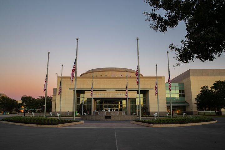 Flags flying at half-staff are seen at the entrance of the George Bush Presidential Library during sunset in College Station,