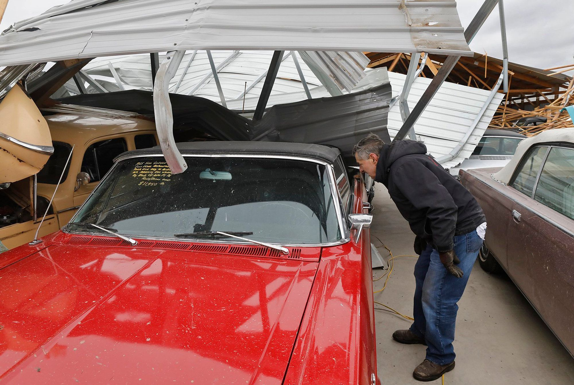 Russ Noel, owner of Country Classic Cars, looks at one of the damaged cars, Sunday, Dec. 2, 2018, at Country Classic Cars nea