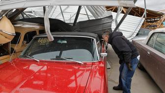 Russ Noel, owner of Country Classic Cars, looks at one of the damaged cars, Sunday, Dec. 2, 2018, at Country Classic Cars near Staunton, Ill. A suspected tornado ripped through the business destroying two buildings and damaging more than 100 cars. (J.B. Forbes/St. Louis Post-Dispatch via AP)