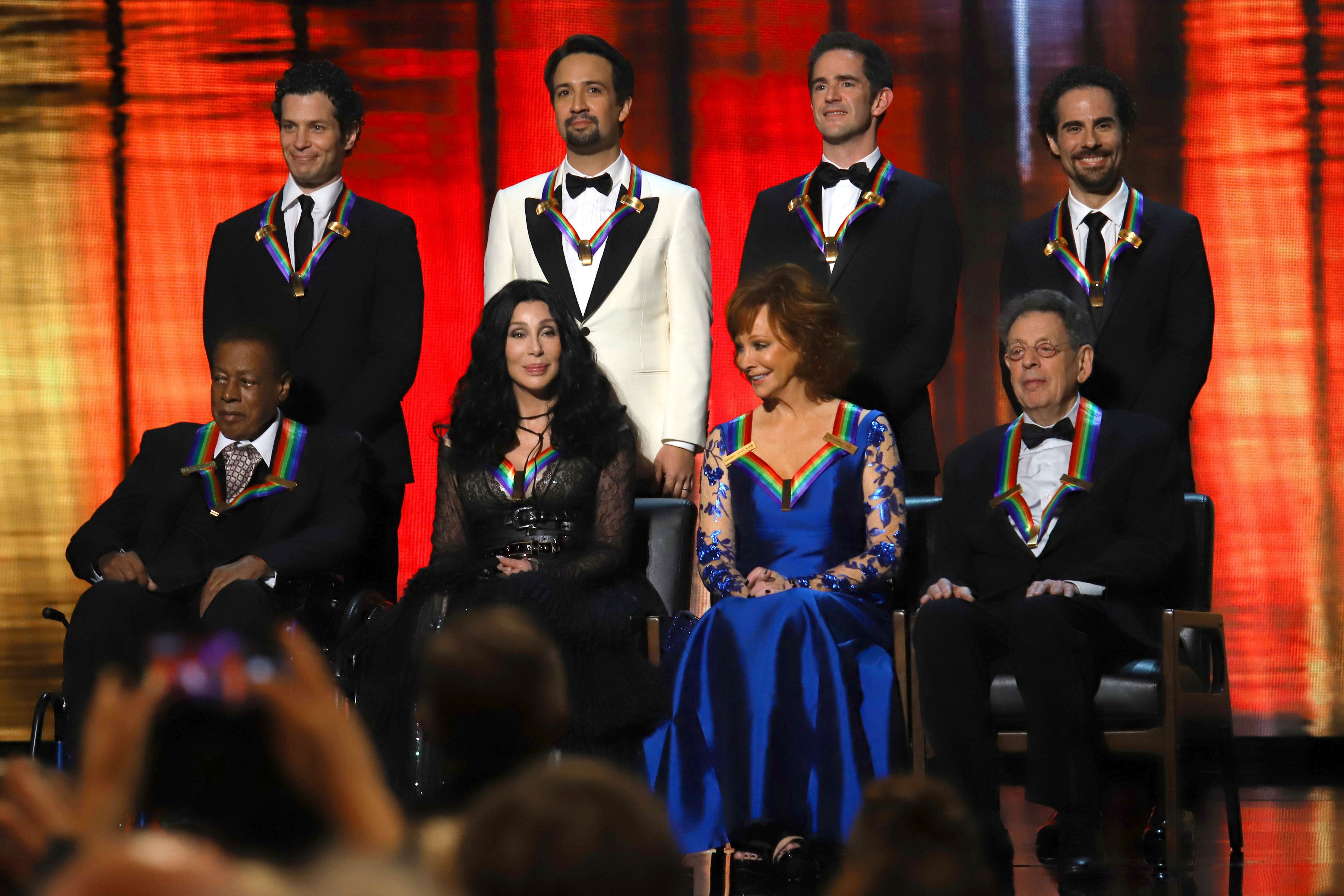"""2018 Kennedy Center honorees, front row from left, Wayne Shorter, Cher, Reba McEntire, Philip Glass; and back row from left, the co-creators of """"Hamilton,"""" Thomas Kail, Lin-Manuel Miranda, Andy Blankenbuehler and Alex Lacamoire appear on stage during the 41st Annual Kennedy Center Honors at The Kennedy Center on Sunday, Dec. 2, 2018, in Washington. (Photo by Greg Allen/Invision/AP)"""