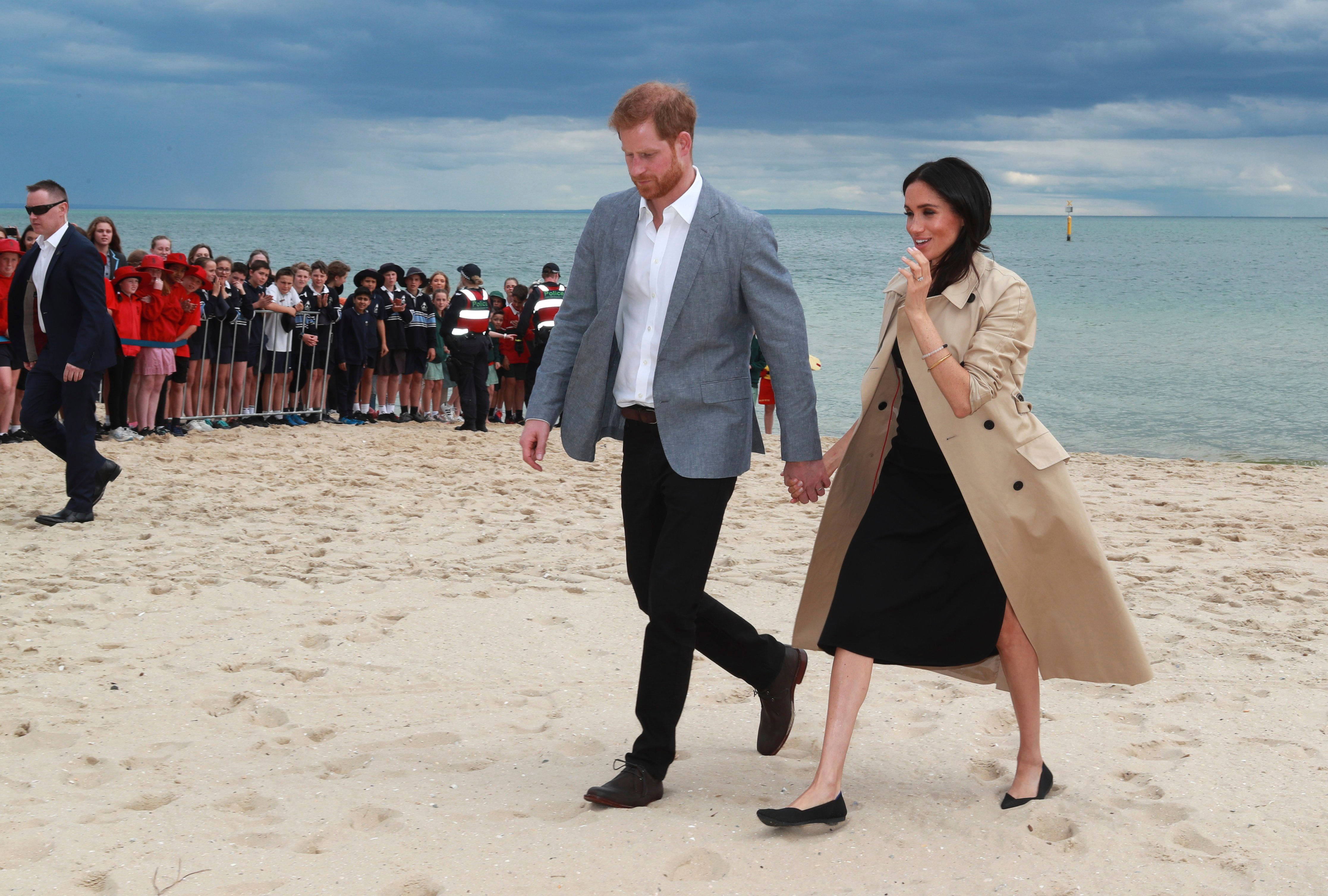 Britain's Prince Harry and Meghan, Duchess of Sussex walk across the sand at South Melbourne Beach in Melbourne, Australia, Thursday, Oct. 18, 2018. Prince Harry and his wife Meghan are on day two of their 16-day tour of Australia and the South Pacific. (Ian Vogler/Pool Photo via AP)