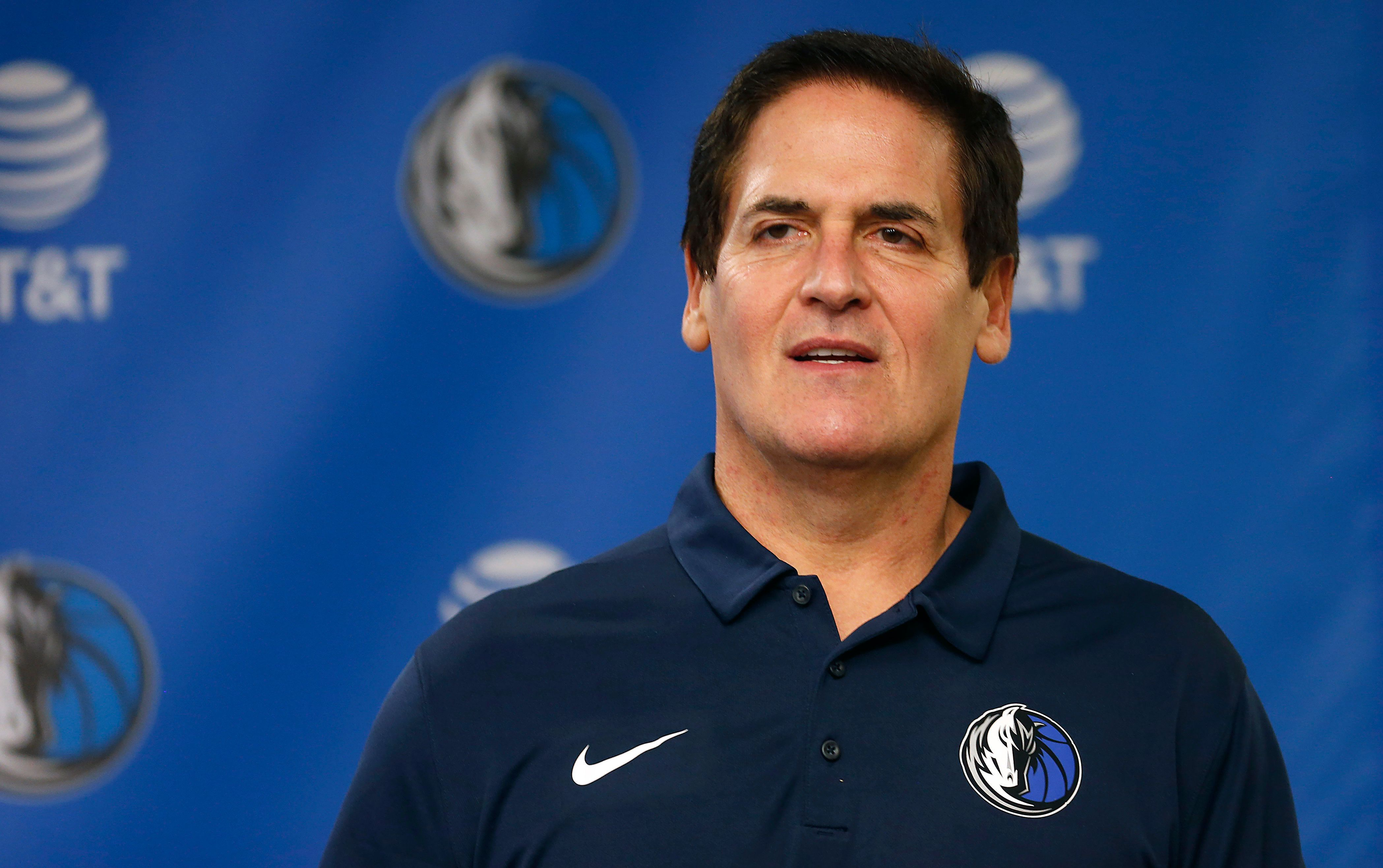 Dallas Mavericks owner Mark Cuban stands on stage before Cynthia Marshall, new interim CEO of the team, is introduced during a news conference, Monday, Feb. 26, 2018, in Dallas. Cuban has teased about the notion of running for president in 2020 in a campaign that could mirror President Donald Trump's blend of reality TV and politics. But Cuban's political career could be quickly derailed by sexual harassment and misconduct allegations within his team. (AP Photo/Ron Jenkins)