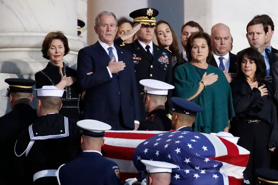 Former President George W. Bush, Laura Bush and other family members watch as a military honor guard carries George H.W. Bush