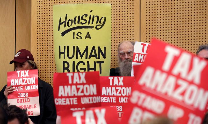 People hold signs at a Seattle City Council meeting on May 14, 2018, to advocate for a tax on large businesses like Amazon an