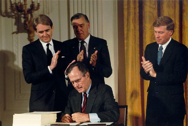 Former EPA Administrator William Reilly watches as the late President Bush signs the Clean Air Act Amendments on Nov. 15, 199
