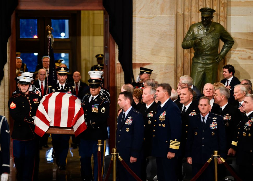 The casket bearing his remains is carried into the Capitol Rotunda.