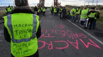 A Yellow vests (Gilets jaunes) protester with the words written of the back of her vest that read, ' Macron (referring to the French President) traitor, the people are hungry' blocks the road leading to the Frontignan oil depot in the south of France, as they demonstrate against the rise in fuel prices and the cost of living on December 3, 2018. - Dozens of French 'yellow vest' demonstrators blocked access to a major fuel depot and several highways on the third week of anti-government protests which led to major riots in Paris at the weekend. (Photo by PASCAL GUYOT / AFP)        (Photo credit should read PASCAL GUYOT/AFP/Getty Images)