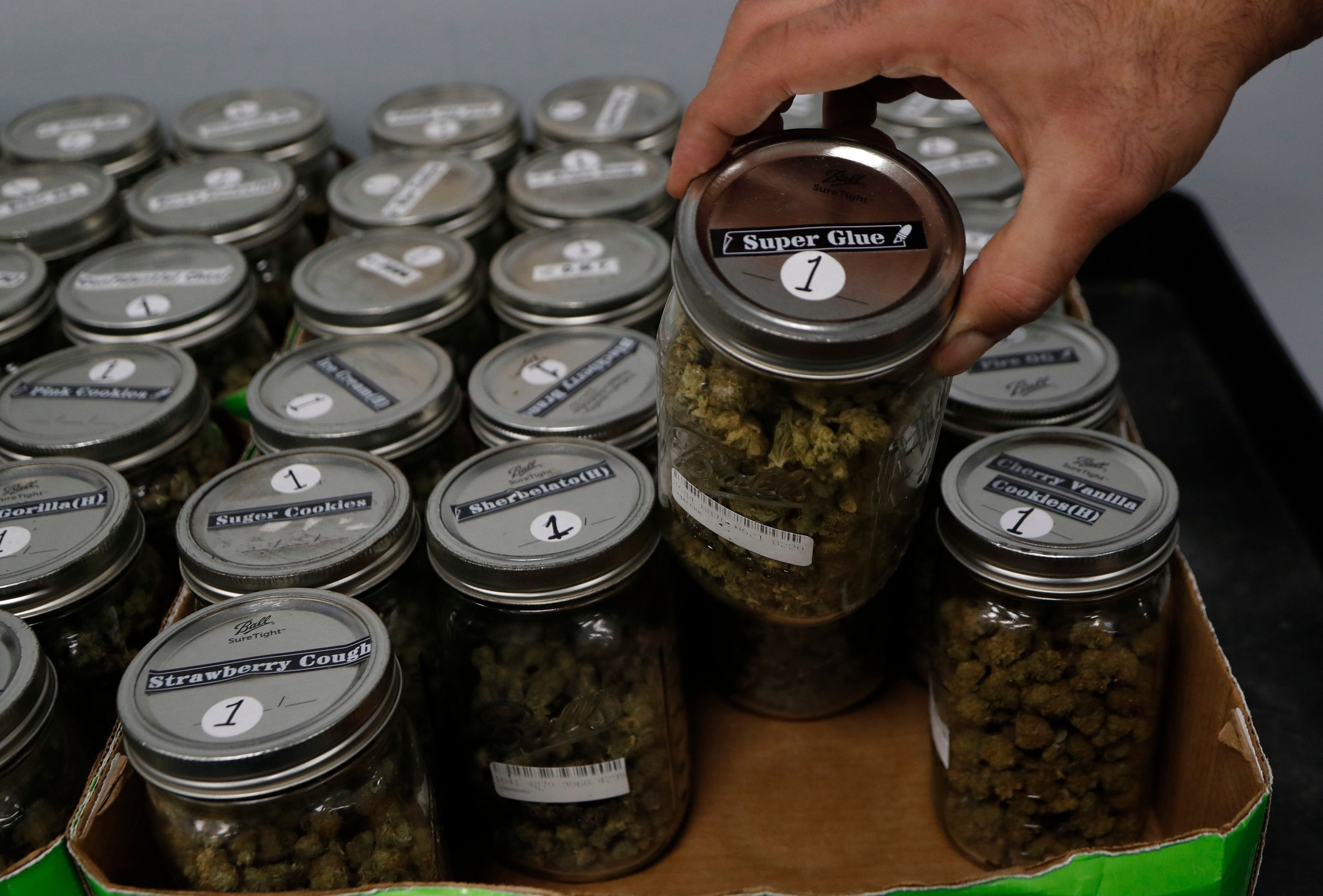 An attendant holds a mason jar of marijuana at a dispensary in Detroit, Michigan, where recreational marijuana has been legal