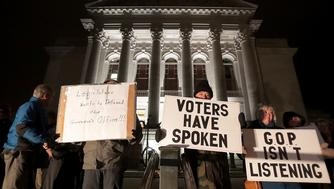Opponents of an extraordinary session bill submitted by Wisconsin Republican legislators gather for a rally outside the Wisconsin state Capitol in Madison, Wis., Monday, Dec. 3, 2018. (John Hart/Wisconsin State Journal via AP)