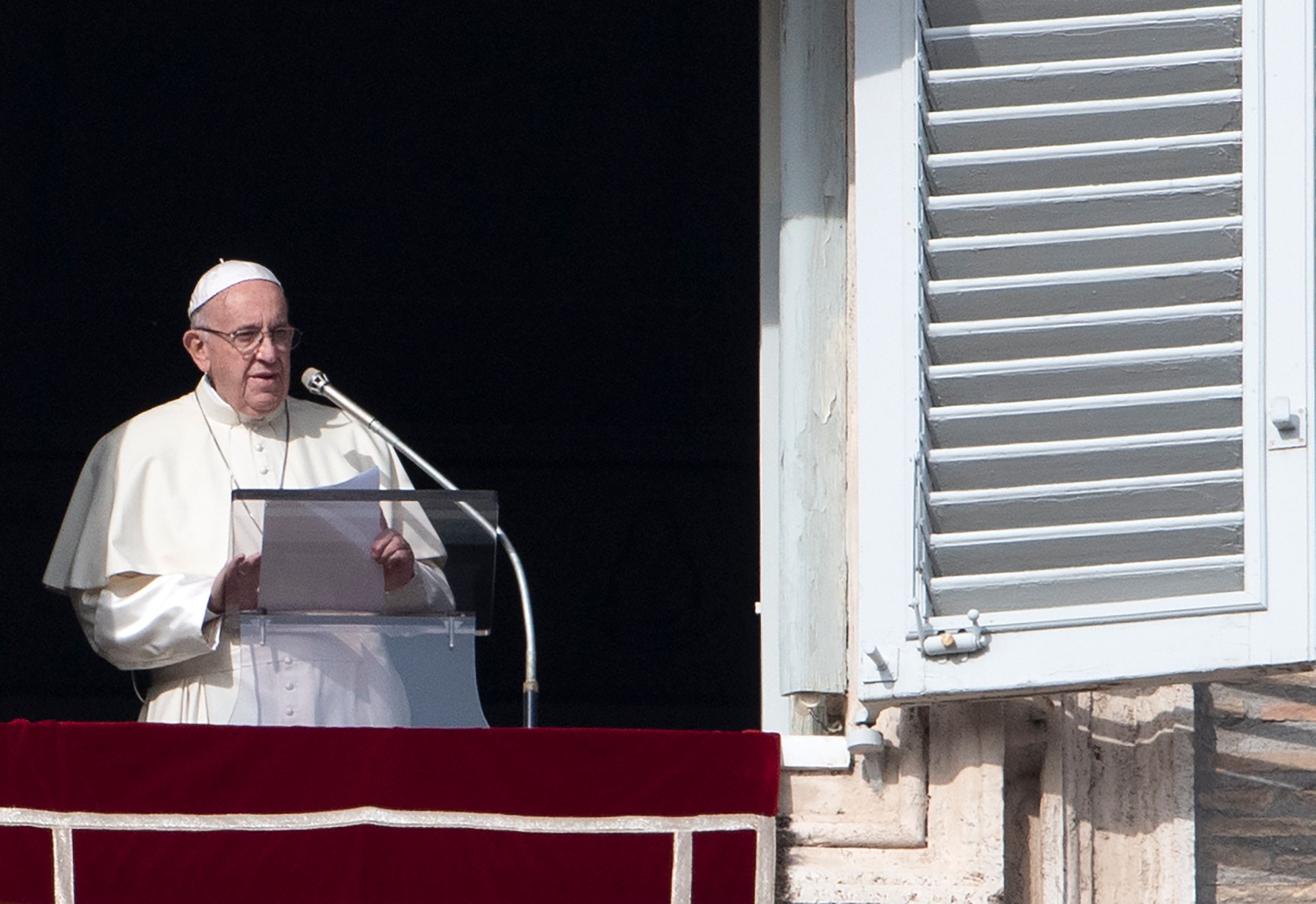 Pope Francis addresses the crowd from the window of the apostolic palace overlooking Saint Peter's...
