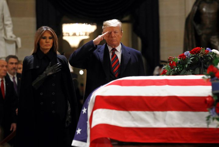 President Donald Trump salutes alongside first lady Melania Trump in front of the flag-draped casket of former President Geor