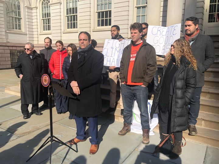 New York City Councilman Costa Constantinides, flanked by housing advocates and environmentalists, announces the introduction