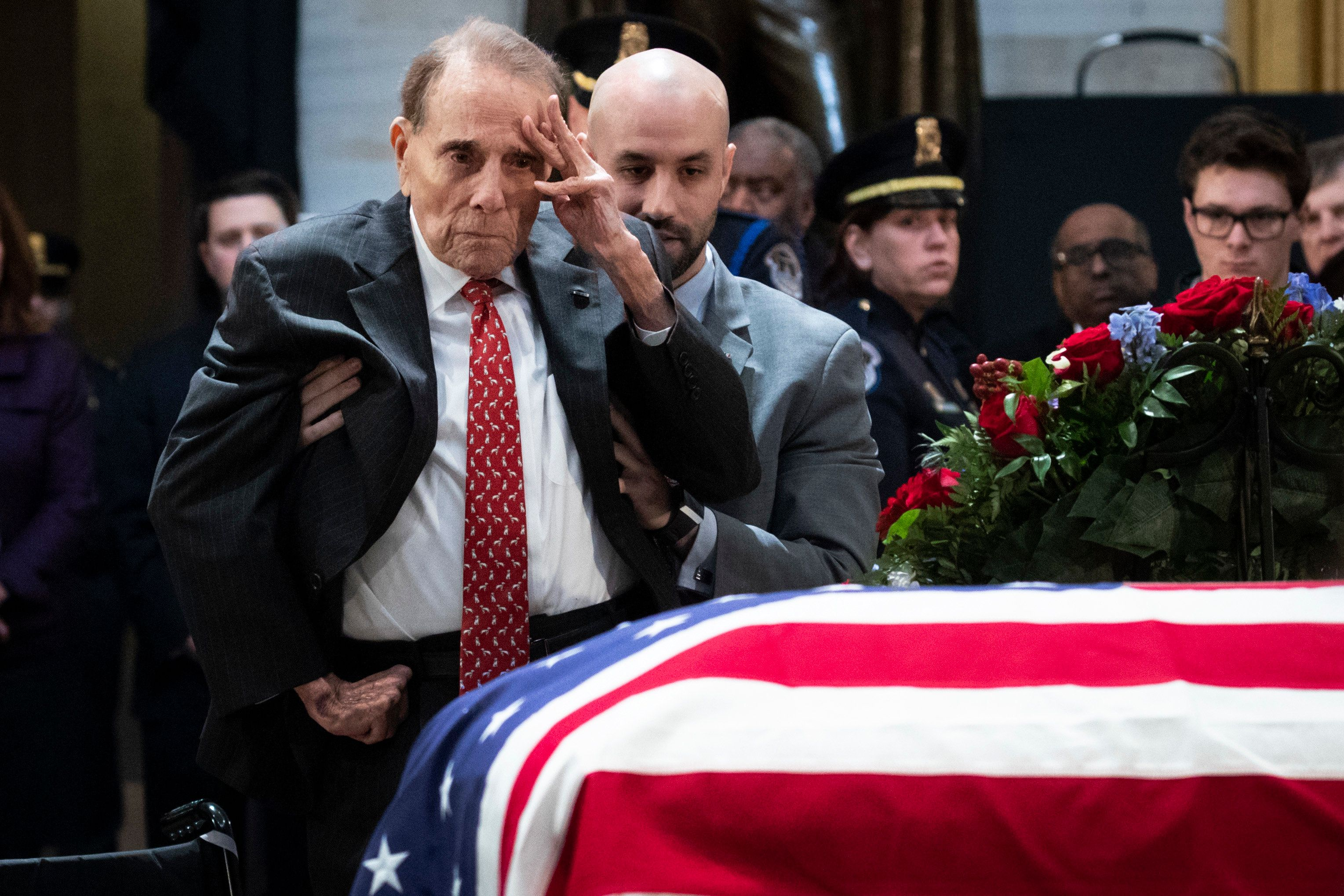 WASHINGTON, DC - DECEMBER 4:  Former Senator Bob Dole stands up and salutes the casket of the late former President George H.W. Bush as he lies in state at the U.S. Capitol, December 4, 2018 in Washington, DC. A WWII combat veteran, Bush served as a member of Congress from Texas, ambassador to the United Nations, director of the CIA, vice president and 41st president of the United States. Bush will lie in state in the U.S. Capitol Rotunda until Wednesday morning. (Photo by Drew Angerer/Getty Images)