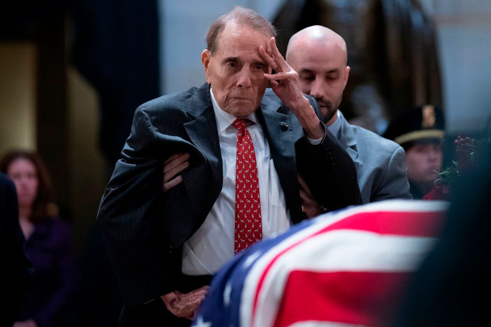 Former Sen. Bob Dole salutes before the flag-draped coffin.