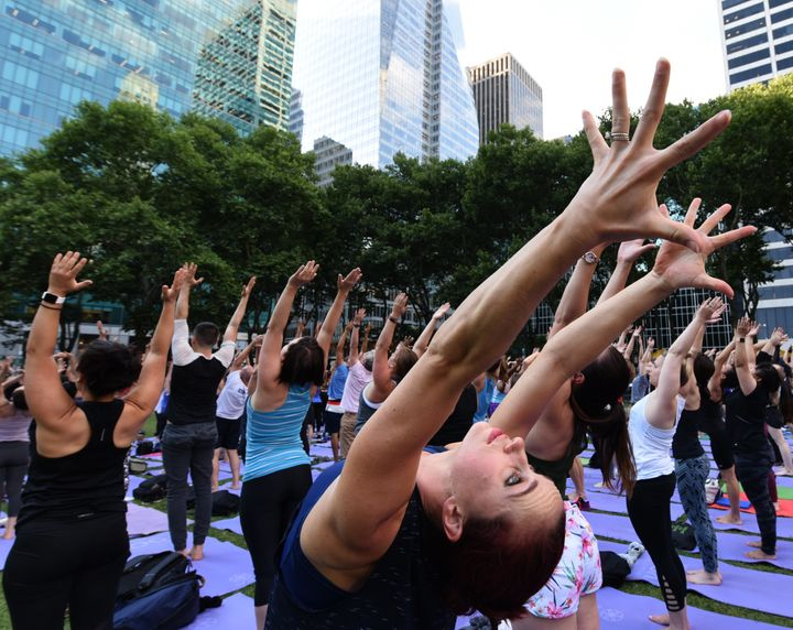 People participate in a free outdoor yoga event in Bryant Park in New York City July 12, 2018. (Photo by TIMOTHY A. CLARY / A