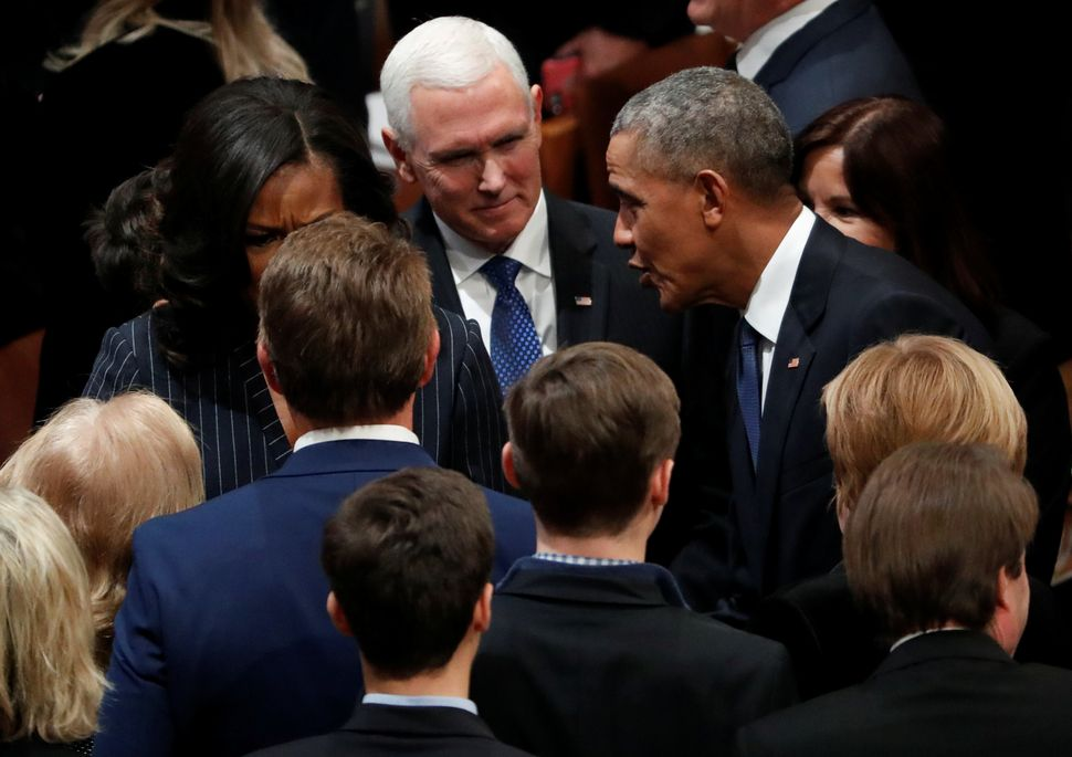Vice President Mike Pence listens to Barack Obama as they gather prior to the state funeral for former Bush.