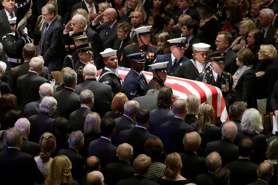 Bush's flag-draped casket is carried by a military honor guard.