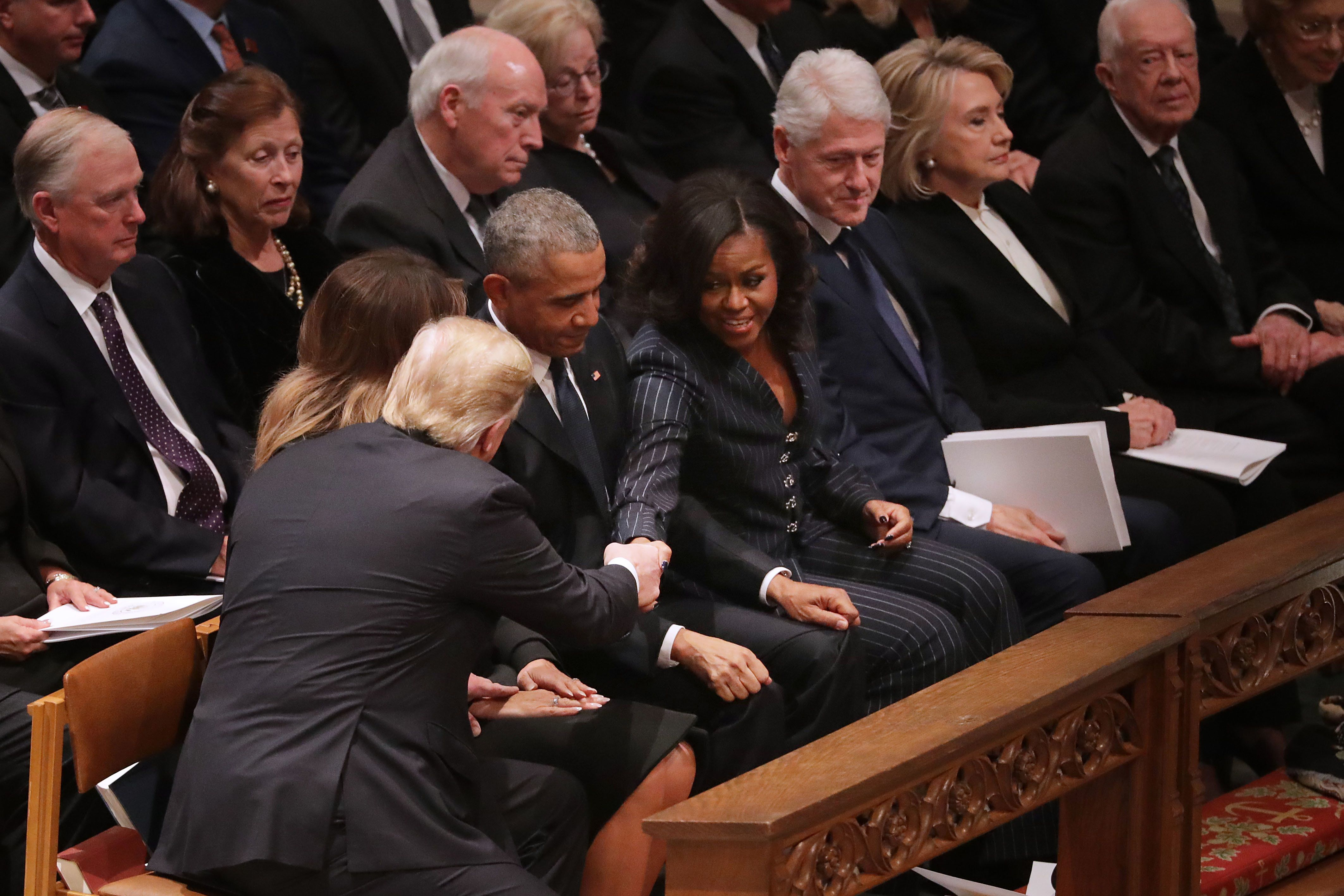 WASHINGTON, DC - DECEMBER 05:  President Donald Trump and first lady Melania Trump greet former President Barack Obama and Michelle Obama as they join other former presidents and vice presidents and their spouses for the state funeral for former President George H.W. Bush at the National Cathedral December 05, 2018 in Washington, DC. A WWII combat veteran, Bush served as a member of Congress from Texas, ambassador to the United Nations, director of the CIA, vice president and 41st president of the United States.  (Photo by Chip Somodevilla/Getty Images)
