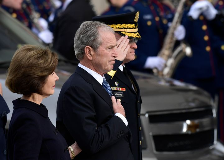George W. Bush is seen beside his wife, Laura Bush, as the casket of his late father arrives at the National Cathedral.