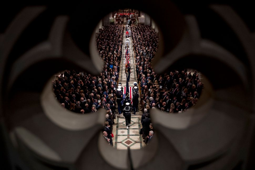 The flag-draped casket of former President George H.W. Bush is carried by a military honor guard into a State Funeral at the
