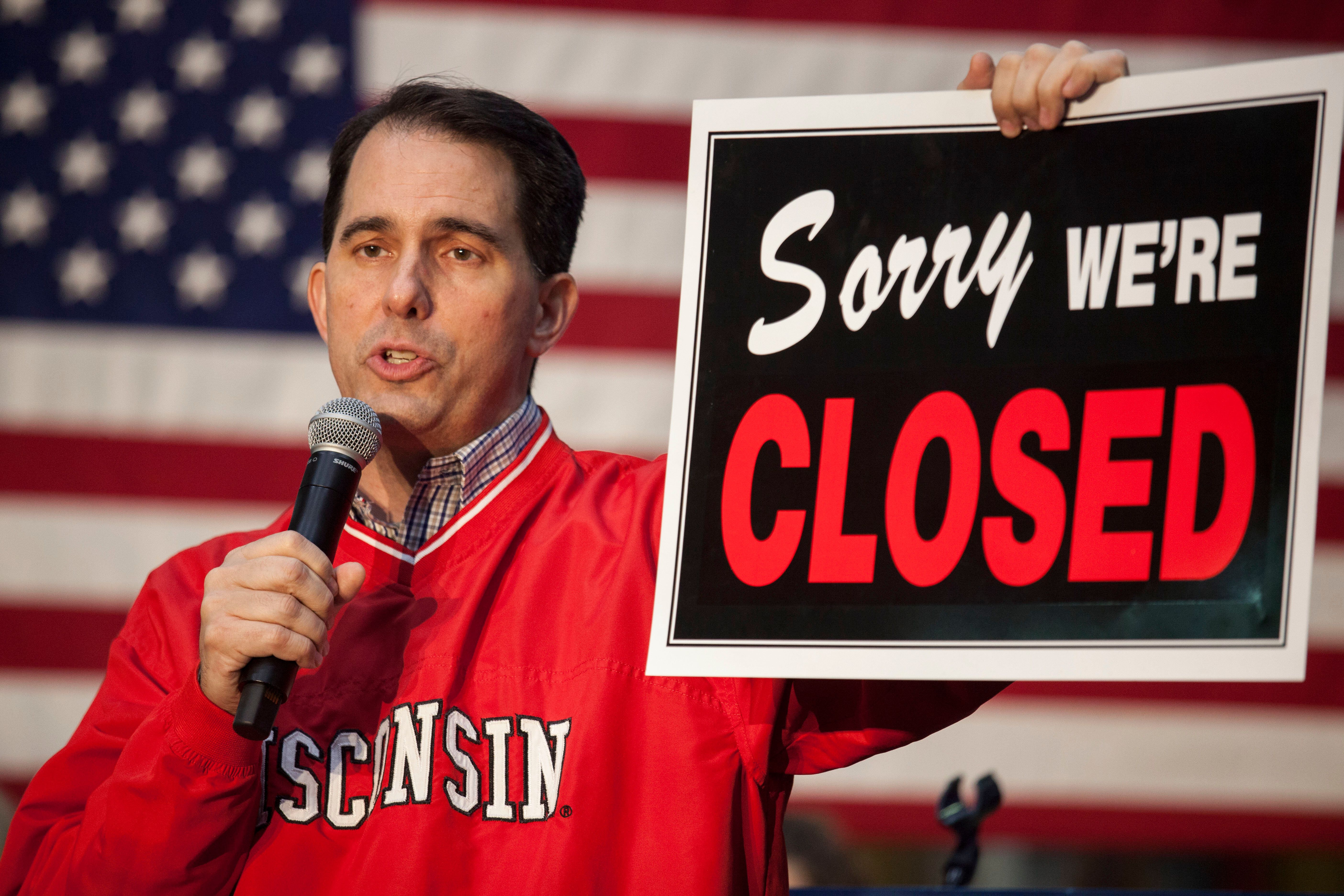WAUKESHA, WI - NOVEMBER 05: Governor Scott Walker (WI-R) holds a sign that reads 'sorry we're closed' as he speaks to supporters at a last minute get out the vote rally the night before the midterm elections at the Weldall Mfg., Inc. on November 5, 2018 in Waukesha, Wisconsin. Incumbent Republican Governor Scott Walker is being challenged for the seat by Democrat Tony Evers in Tuesday's midterm elections. (Photo by Darren Hauck/Getty Images)